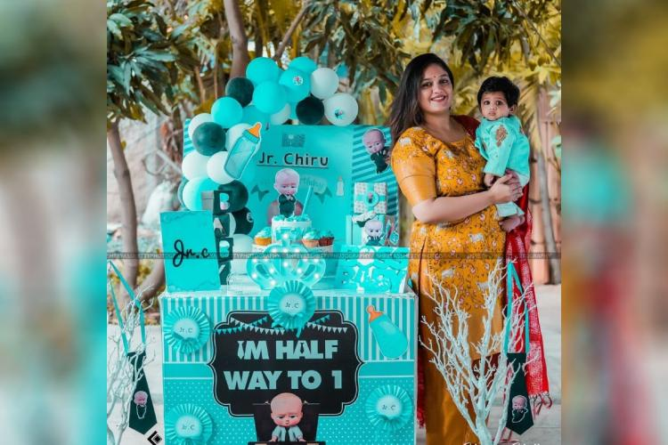 Meghana Raj is seen holding Jr Chiru who is dressed in blue ethnic clothes cake baloons and other decoration items are seen in the background