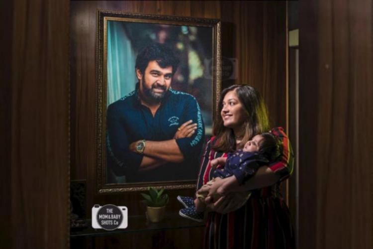 Meghana Raj is seen holding Jr Chiru while Chiranjeevis photo is visible in the background