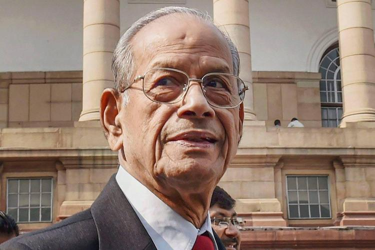 Sreedharan in a black suit looks afar and in the background is a cream and white building