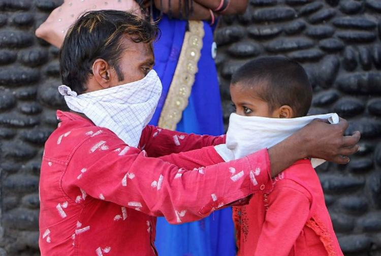 A migrant worker ties a cloth as mask for his child