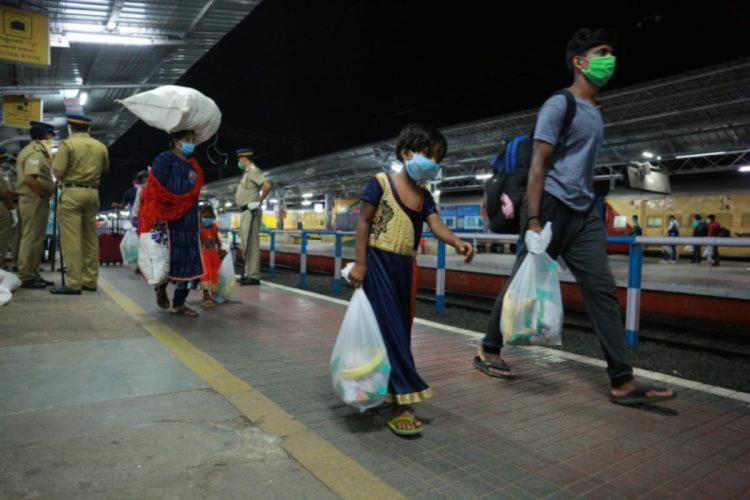 A migrant labourer along with a girl child walking in a railway station
