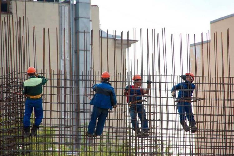 Four construction workers on a scaffold at a construction site They are seen in their protective gear including helmets and reflective safety jackets Parts of other buildings are seen in the background