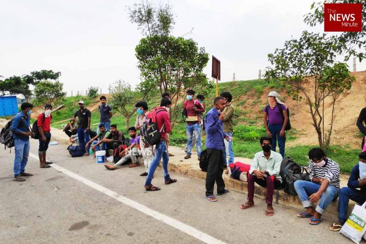 Migrant workers walking home stop at the side of a road in Bengaluru