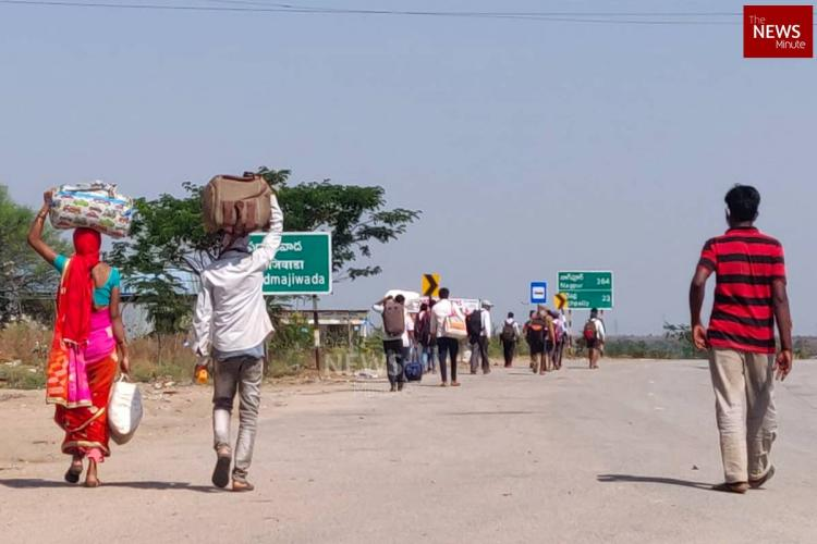 A group of migrant workers carrying their belongings over their heads and walking on a highway amid the nationwide lockdown