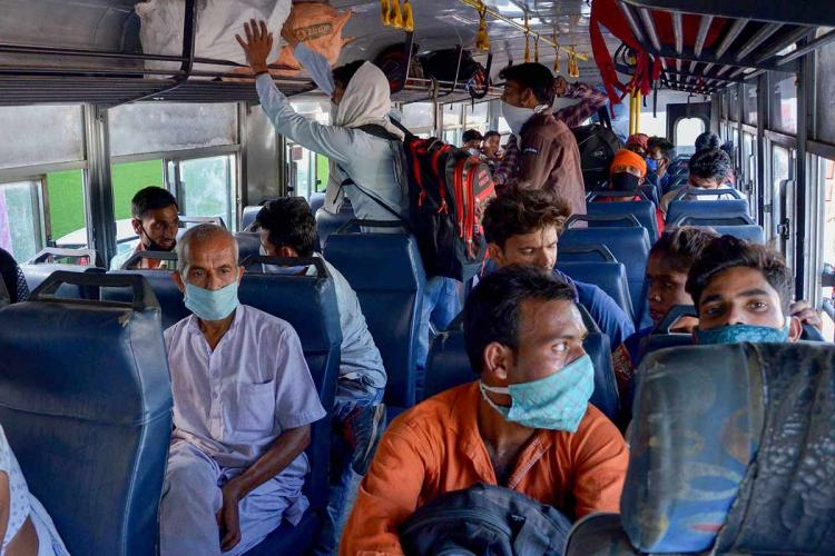 Migrant workers wearing masks in a bus in Amritsar