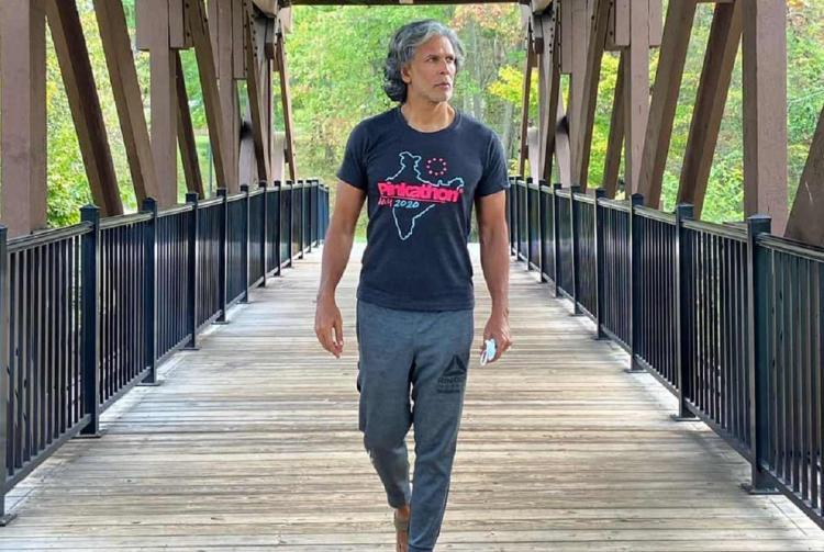 Milind Soman walking on a bridge