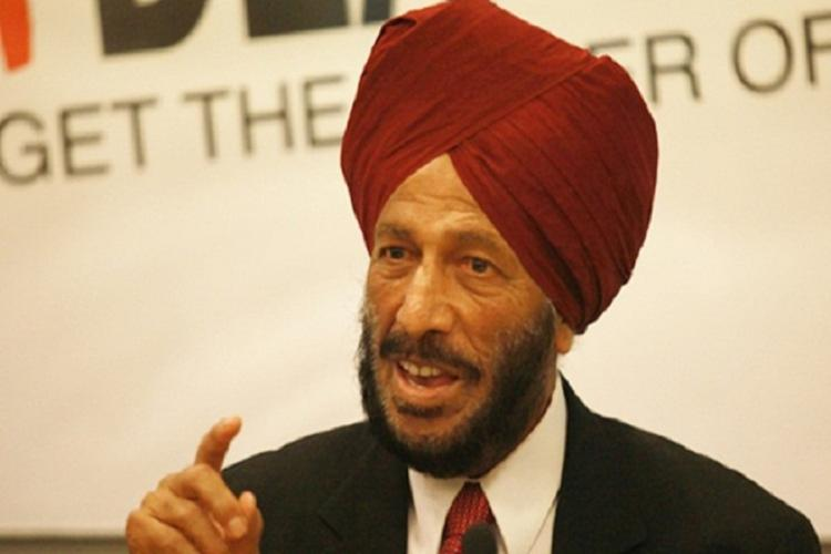 Milkha singh talking to someone by wearing a black coat and red turban