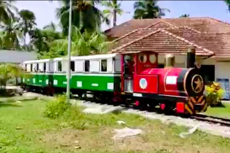 A red and green mini train chugging across a track