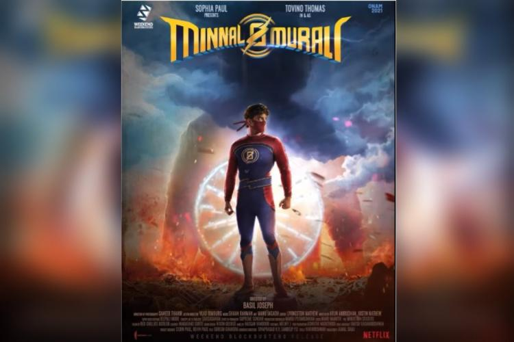 A man in superhero costume stands looking at his right and in the background are blue and brown shades in the dark on top is the title of the film Minnal Murali