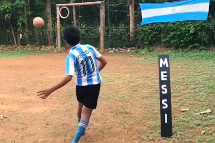 Boy kicking a football into the goalpost