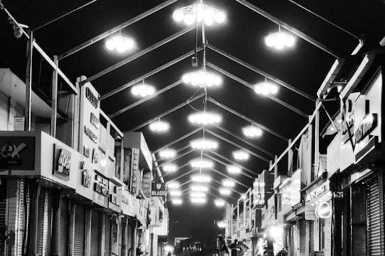 Black and white photo of SM Street in Kozhikode with lights on top