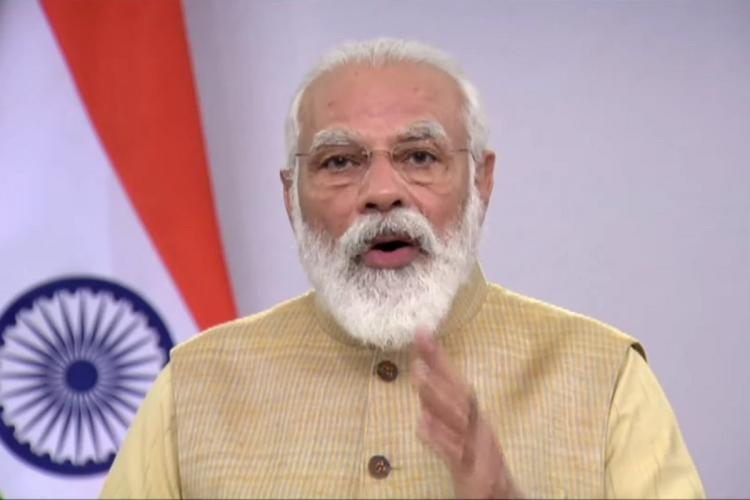 PM Modi wearing a cream Nehru jacket addresses India Ideas Summit via video conferencing with an Indian flag on the left corner of the screen