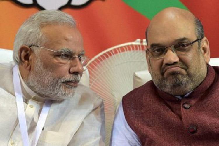PM Narendra Modi and HM Amit Shah seated next to each other at an event. Modi is leaning in to speak to Shah as Shah looks straight ahead.
