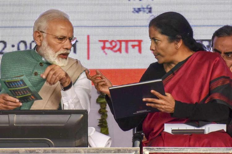 A picture of Prime Minister Narendra Modi and Finance Minister Nirmala Sitharaman, talking to each other while sitting on state. Modi is wearing a green jacket and is on the left of the frame. Nirmala is in a red sari, holding a black folder, and is on the right of the frame.