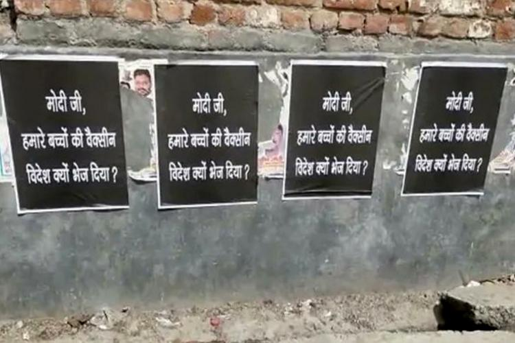 Four posters pasted on a wall in New Delhi The poster with black background and white font reads Modiji humare bachon ki vaccine videsh kyu bhej diya PM why did you send vaccines of our children to foreign countries