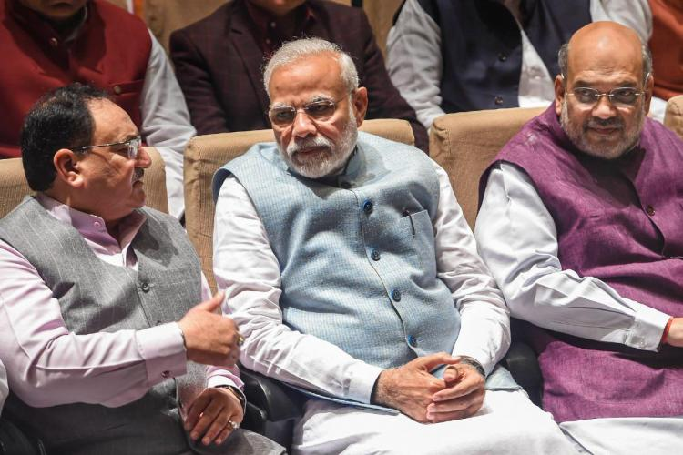 JP Nadda Narendra Modi and Amit Shah seated next to each other engaged in a discussion