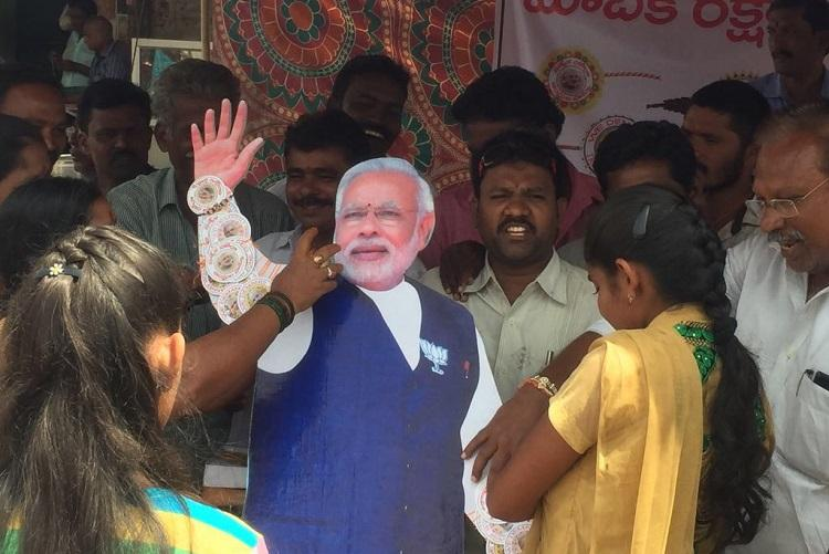 In Pictures Vizag women tie rakhi on PM Modi cut-out demanding special status for Andhra Pradesh