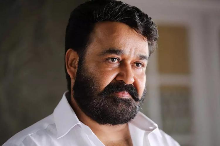 Bearded Mohanlal wearing white looks sideways