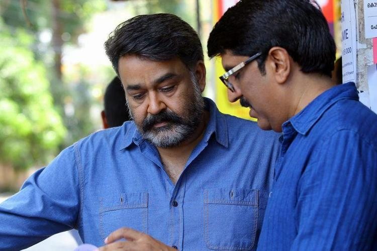 Mohanlal and B Unnikrishnan in blue shirts the latter narrating to the actor