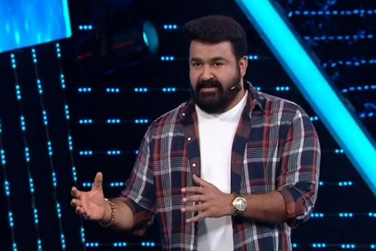 Mohanlal is seen wearing a white tee and multicoloured checked shirt and is seen hosting Bigg Boss in the image