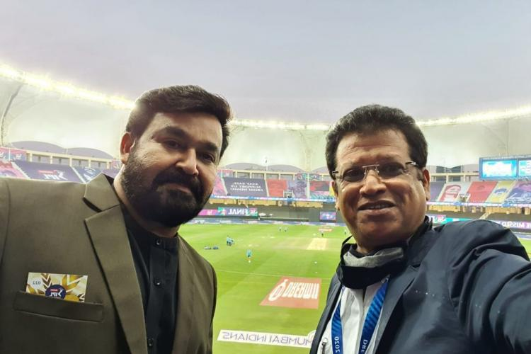 Mohanlal in a green suit and a beard poses with another man and in the background can see the cricket ground