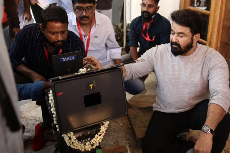 Mohanlal sporting a beard and wearing a full sleeve off white t shirt checks the laptop as others including B Unnikrishnan watch