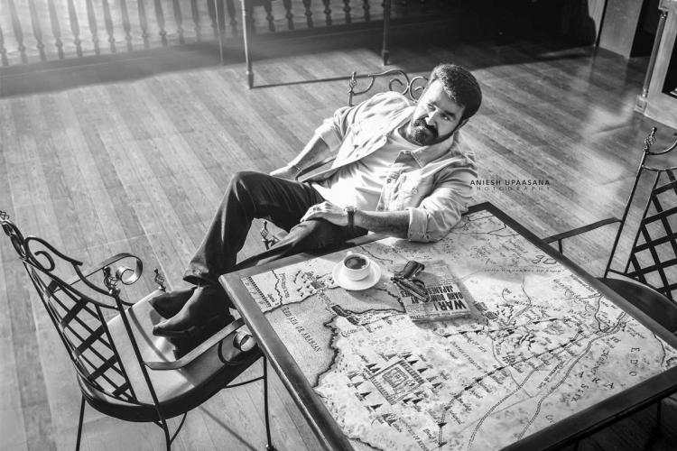 Mohanlal in a black and white picture sits casually on a chair resting his feet on another next to a table