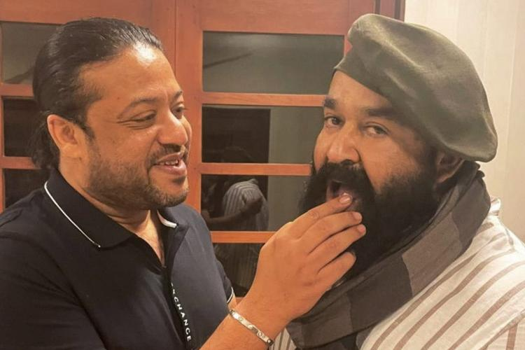 Mohanlal is seen eating his birthday cake and is sporting a new look in a long beard with a scarf and French hat