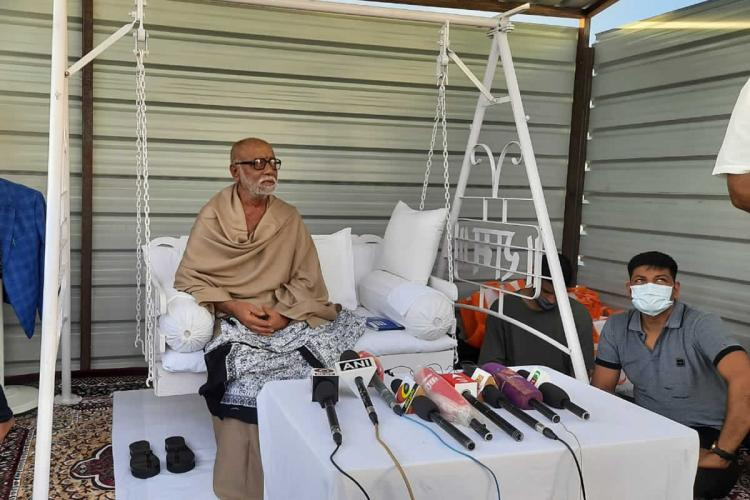 Morari Bapu wearing a beige shawl sitting on a white metal swing at a press conference for his event in Dhanushkodi Tamil Nadu
