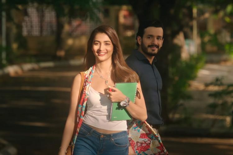 Pooja Hegde walking ahead as Akhil Akkineni stands behing and looks at her