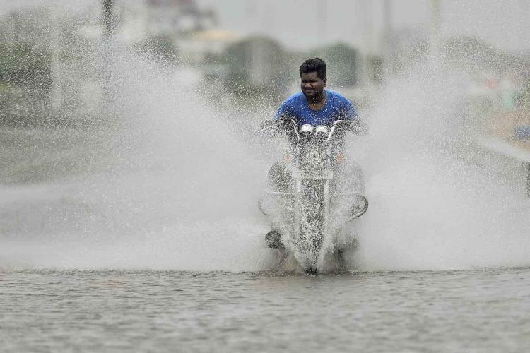 A motorist rides through a waterlogged road after heavy rain in Chennai