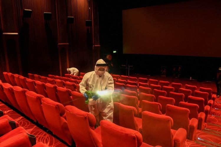 A person sanitising a Movie Theatre