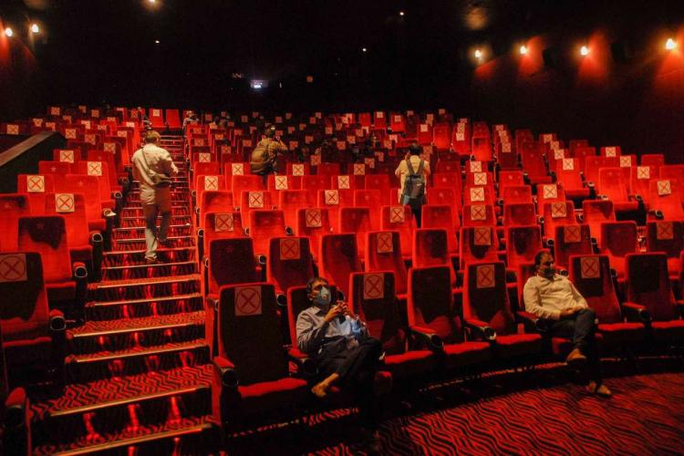 People watch a movie at Carnival Cinemas after it reopened for visitors during Unlock 5 amid the coronavirus pandemic at GIP Mall in Noida