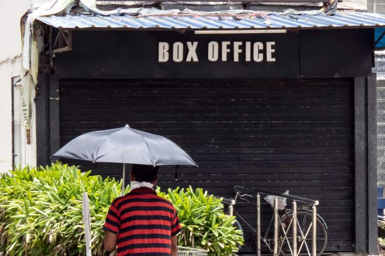A movie theater ticket counter which is closed and a man passing through it using an umbrella in rain