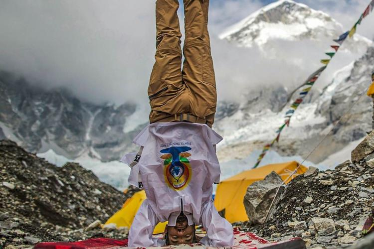 Man stands upside down at the gateway of the snow covered Mt Everest