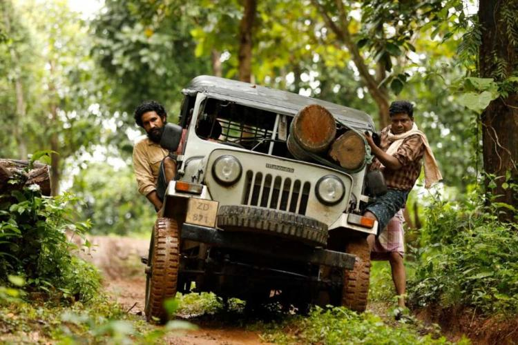 Two men in a jeep carrying logs driving through a green forest