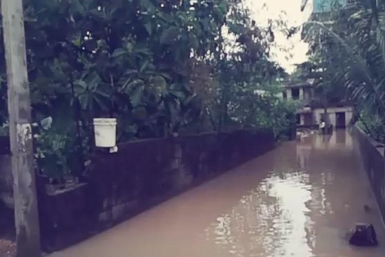 Homes flooded residents of this Tvm colony wait in autorickshaws for water to recede
