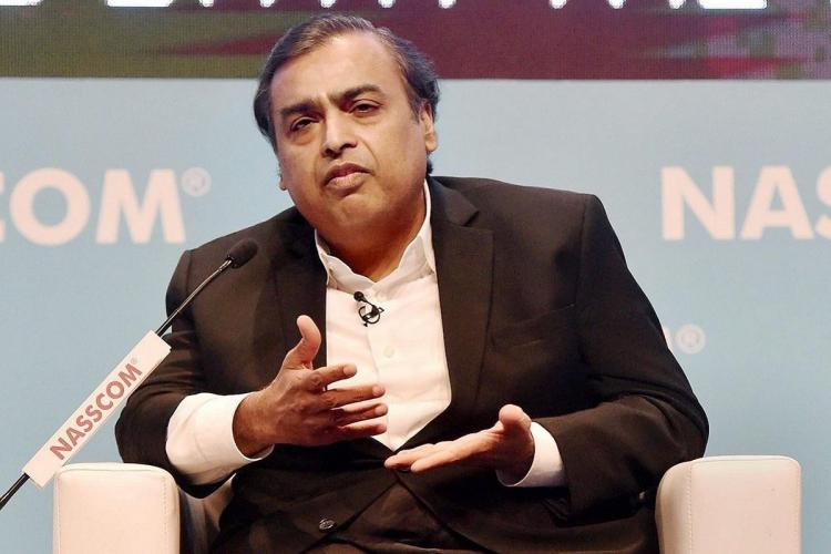 Mukesh Ambani wearing a black suit and speaking at an event