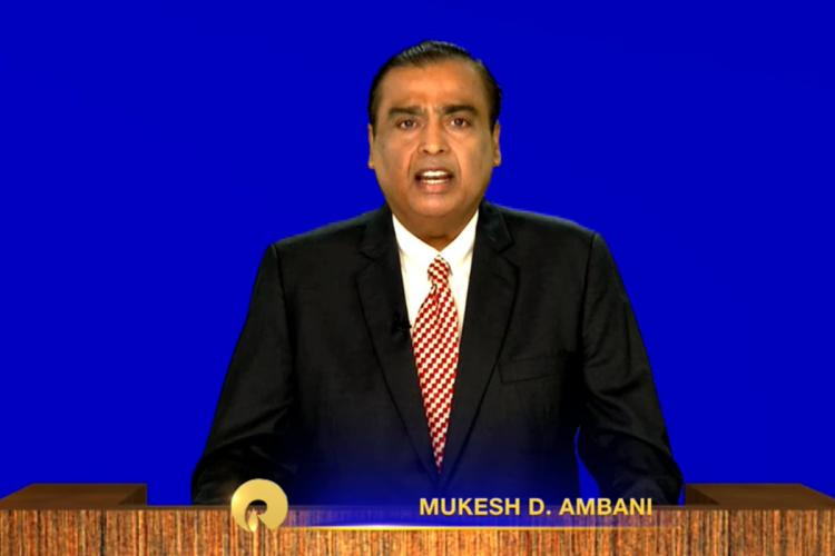 Reliance Industries Chairman Mukesh Ambani stands behind a podium and in front of a blue screen wearing a black suit and a red-checked tie