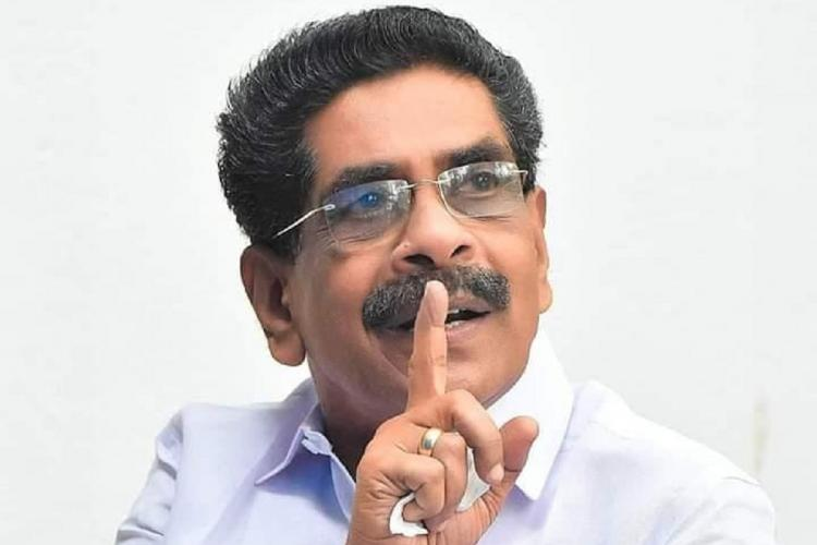 Mullappally in white shirt and specs with his right hand in a gesture in front of his face as he looks up at someone