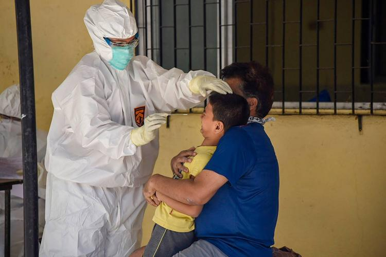 A medical personnel in PPE suit collecting a swab from a kid