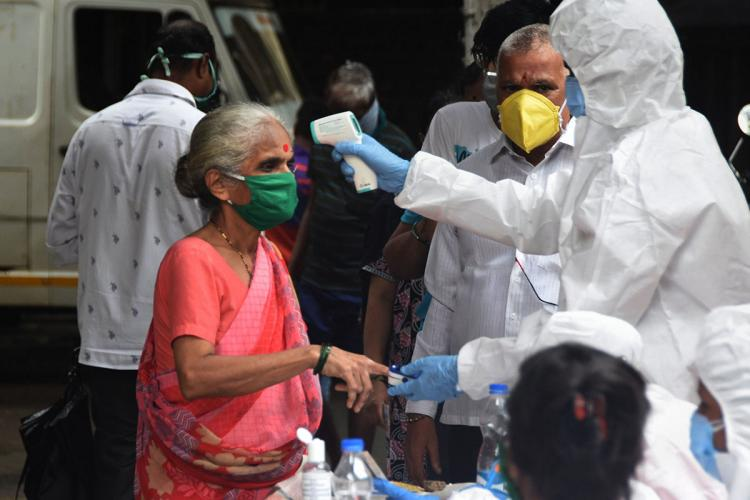 An elderly woman having her temperature checked by a health worker in a PPE suit on the street as people watch