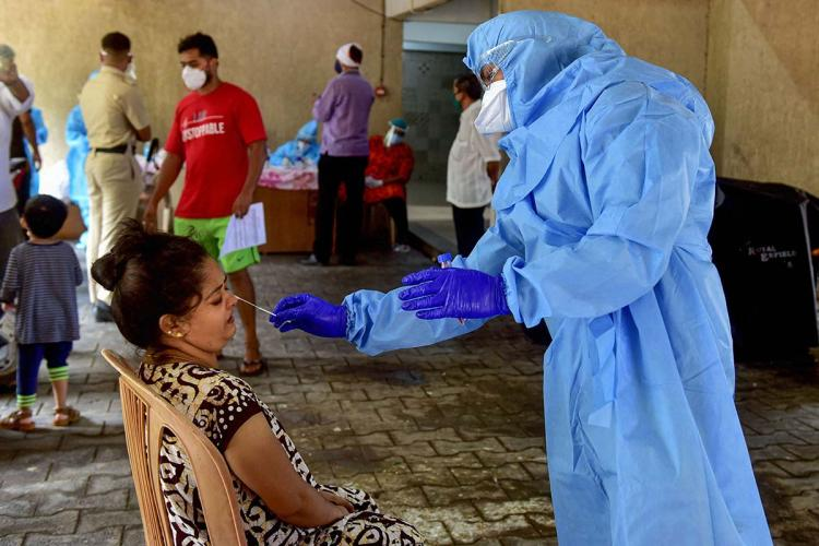 person in PPE takes a swab sample from a woman seated in a plastic chair