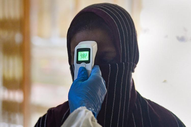 Health worker screening a resident for temperature