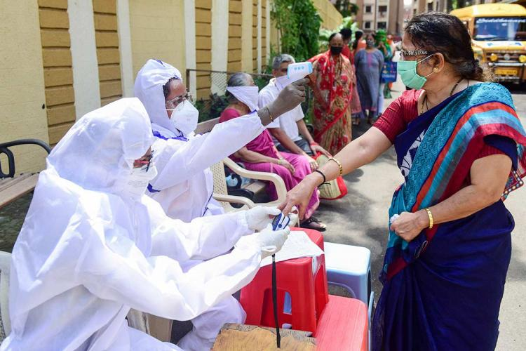 Health workers in personal protective equipment checking temperature of a woman clad in saree. The two health workers are sitting on the sides of a lane in a chair. Few other senior citizens are also waiting in line to undergo temperature check.