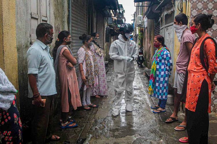 Medic in white hazmat suit talking to a few people standing in a street