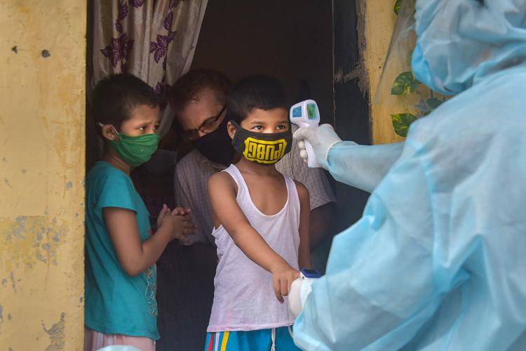 Health official in PPE takes a childs temperature with a hand held device at the door of his house