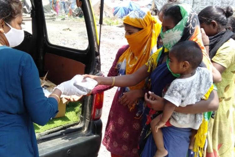 A woman hands out packets of food in Mumbai during COVID-19 restrictions