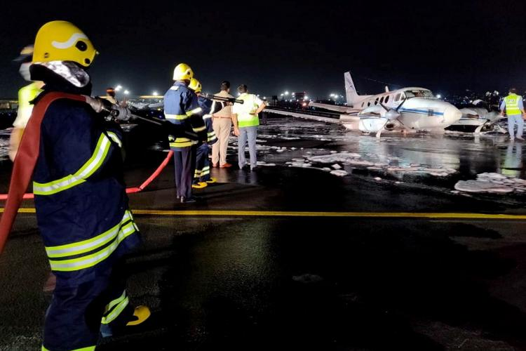 Rescue personnel spread foam as an air ambulance lands at Mumbai airport in the night