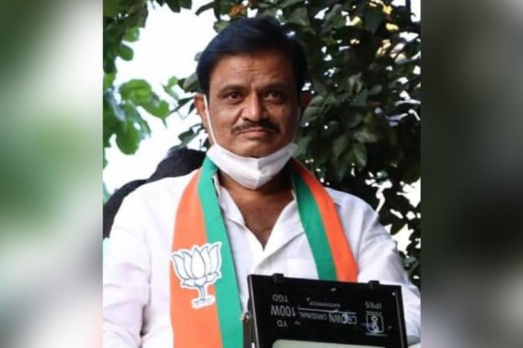 Munirathna Naidu wearing a white shirt with a scarf containing BJPs logo He is wearing his face mask on his chin
